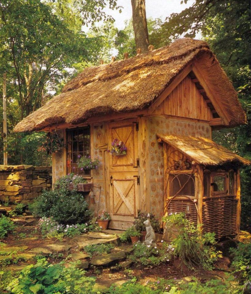 cordwood garden shed with a thatched roof and rabbit hutch on the ...